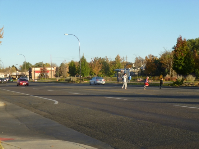 Pedestrians running across 58th Avenue across from McDonald's during  a break in traffic